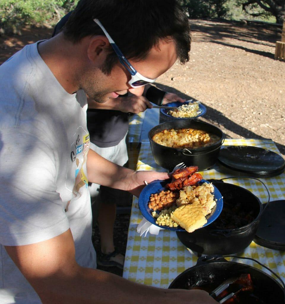 man eating food while camping