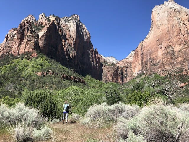 a woman practices social distancing in zion national park